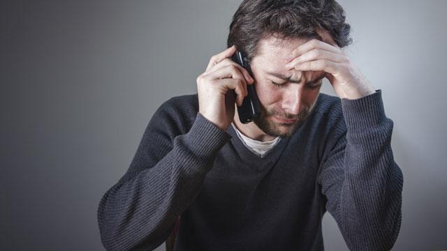 Weinender Mann am Telefon