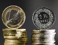 Ein Stapel Ein-Franken-Münzen neben einem Stapel Ein-Euro-Münzen