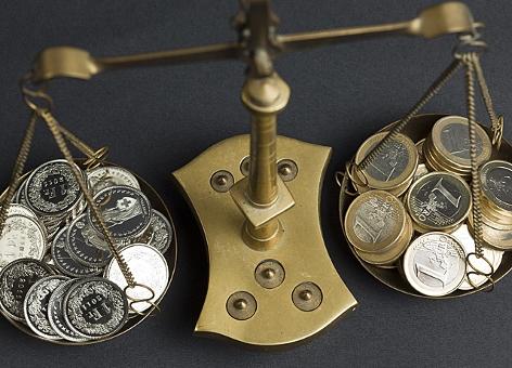 Waage mit Euro- und Frankenmünzen in den Waagschalen