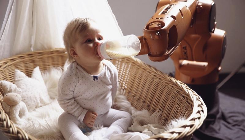 Serien-Still von Homo Digitalis: ein Baby bekommt das Fläschchen von einem Roboter