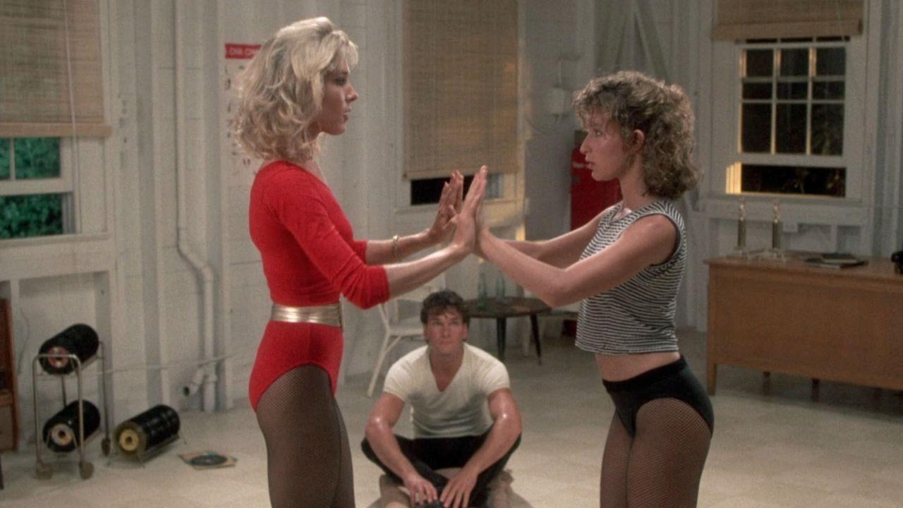"Zwei Frauen tanzen, ein Mann sitzt am Boden, Szenenbild aus ""Dirty Dancing"""