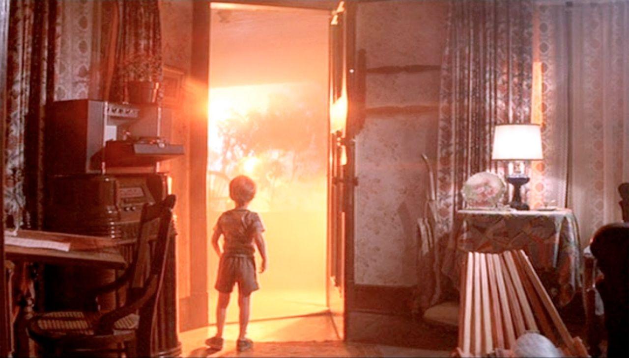 """Still aus """"Unheimliche Begegenung der dritten Art"""", kleines Kind öffnet die Haustür, dahinter helles Licht"""