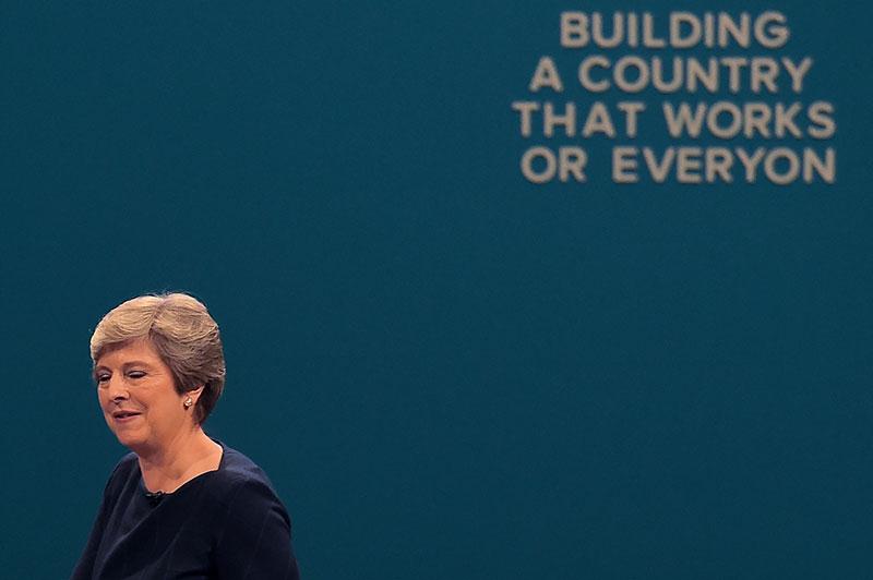 Theresa May unter einem Slogan, aus dem schon ein paar Buchstaben herausgefallen sind