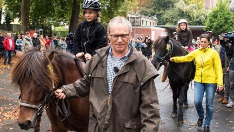 Opa mit Enkelkindern und Pferden vor der Schule