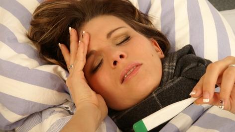 Junge Frau liegt mit Fieberthermometer im Bett