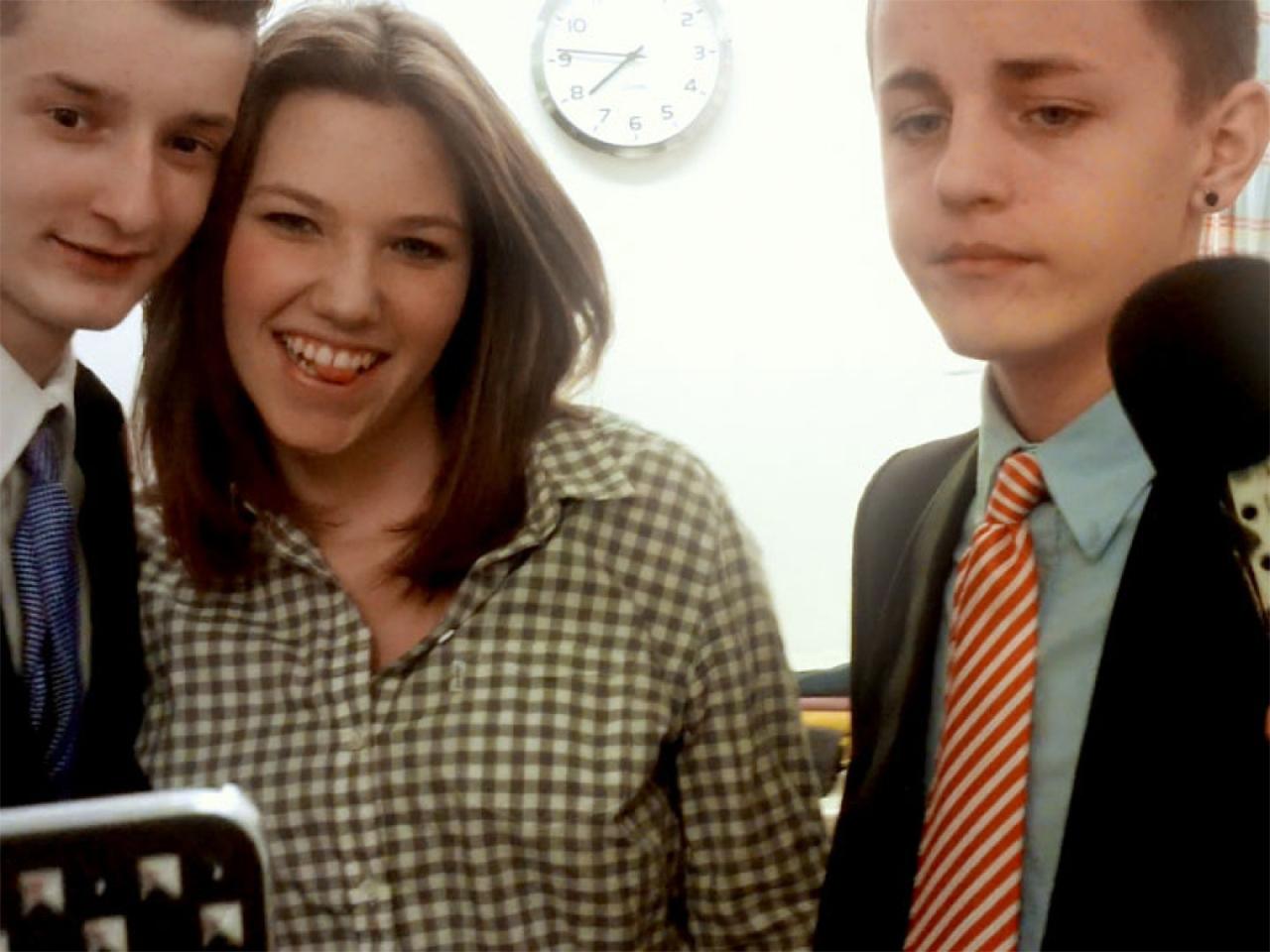 Schüler und eine Schülerin mit Handy