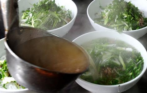 Suppenschüsseln auf einem Tisch, die mit einer Suppenkelle befüllt werden
