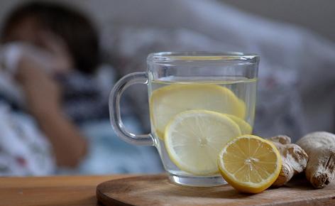 Eine Tasse mit aufgeschnittenen Zitronen und Ingwer liegen auf einem Tisch. Im Hintergrund liegt eine Frau in einem Bett und schneuzt sich die Nase.