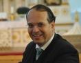 Pfarrer Krömer lächelnd in einer Kirchenbank