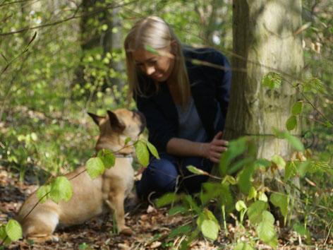 Eine Frau mit Hund bei einem Baumgrab