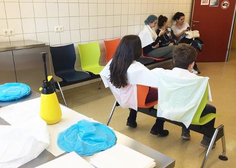 Zwei Kinder warten im Hygienezentrum der Stadt Wien darauf, mit dem Anti-Lausmittel eingesprüht zu werden