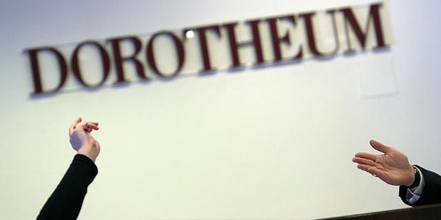 Hände bei einer Versteigerung im Dorotheum vor dem Schriftzug