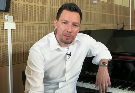 Dirigent Lorenz Aichner sitzt an einem Flügel
