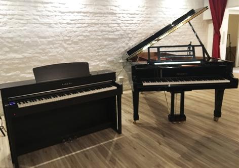 Die beiden Kontrahenten: Das Digitalpiano steht neben dem Flügel, beide sind schwarz