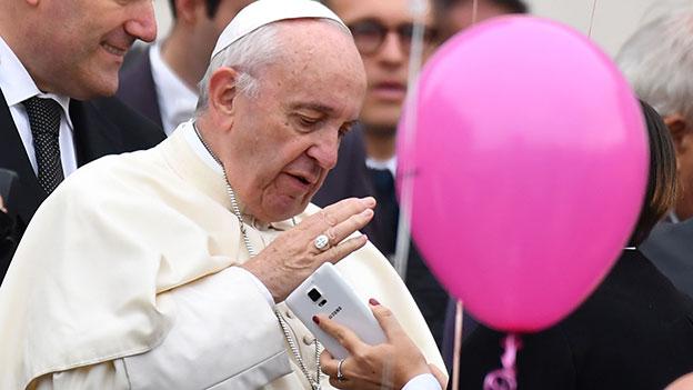 Papst Franziskus währt ein Smartphone ab - neben ihm ist ein pinker Luftballon