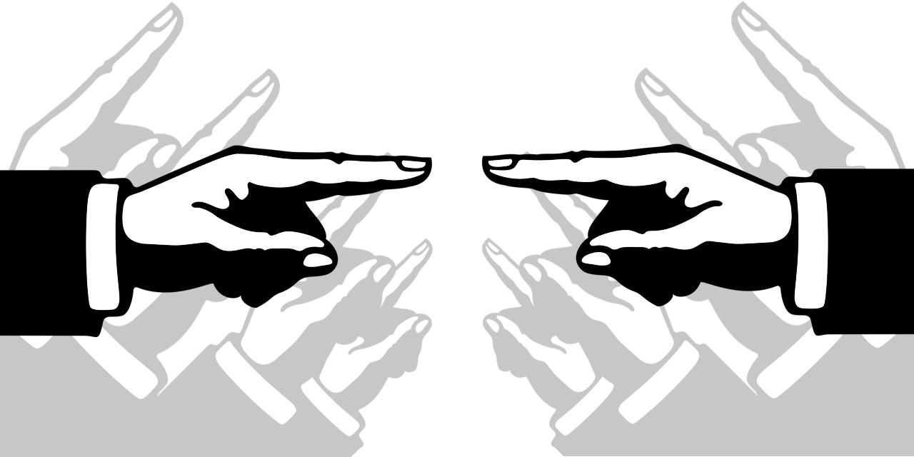 Zeigefinger zeigen aufeinander, im Hintergrund weitere, die wie aufgereihte Kanonen aussehen