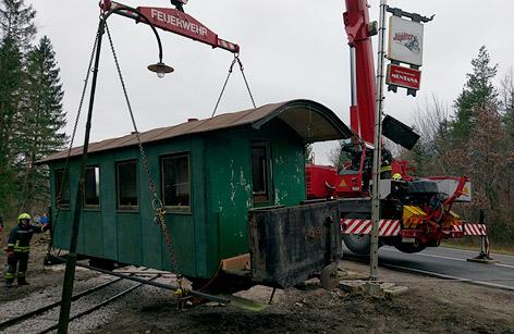 Ein Eisenbahnwaggon wird auf einen Schwerlaster geladen.