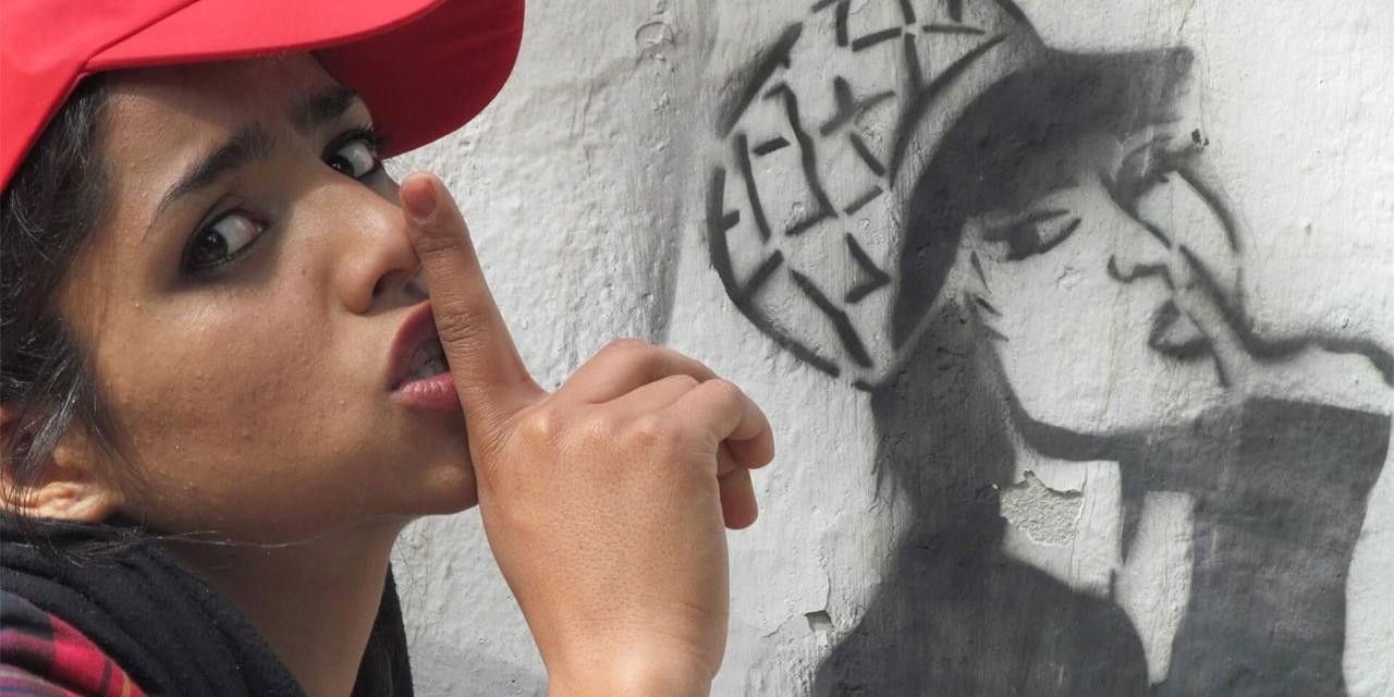 Frau mit Zeigefinger vor dem Mund posiert vor Graffitti von Frau mit Zeigefinger vor dem Mund