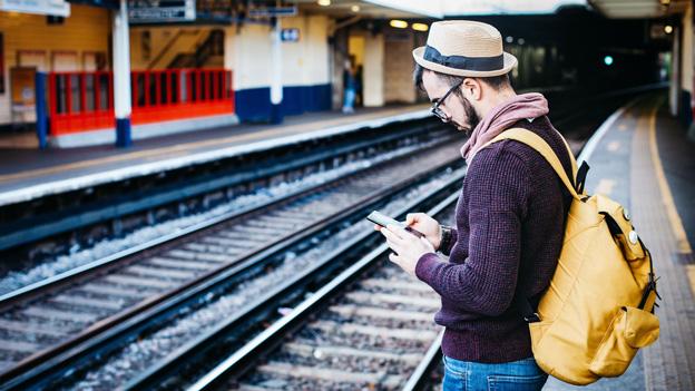 Mann mit Handy am Bahnsteig