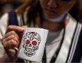 Eine Frau schaut skeptisch in ihr Kaffeeheferl