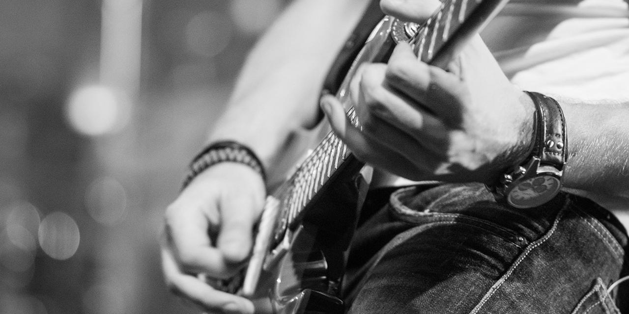 Hände von einem Mann eine E-Gitarre spielend