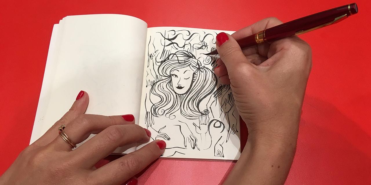 Die Comiczeichnerin Pénélope Bagieu beim Zeichnen, man sieht ihre Hände, wie sie einen Frauenkopf zeichnet