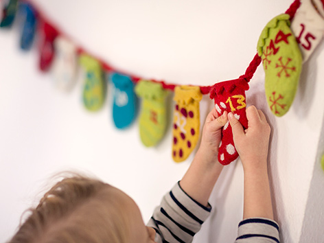 Ein Kind berührt ein Adventkalender-Sackerl
