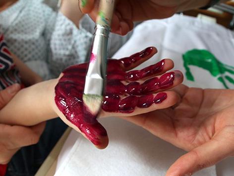 Eine Kinderhand wird angemalt - Sujet Familien im CS Hospiz Rennweg