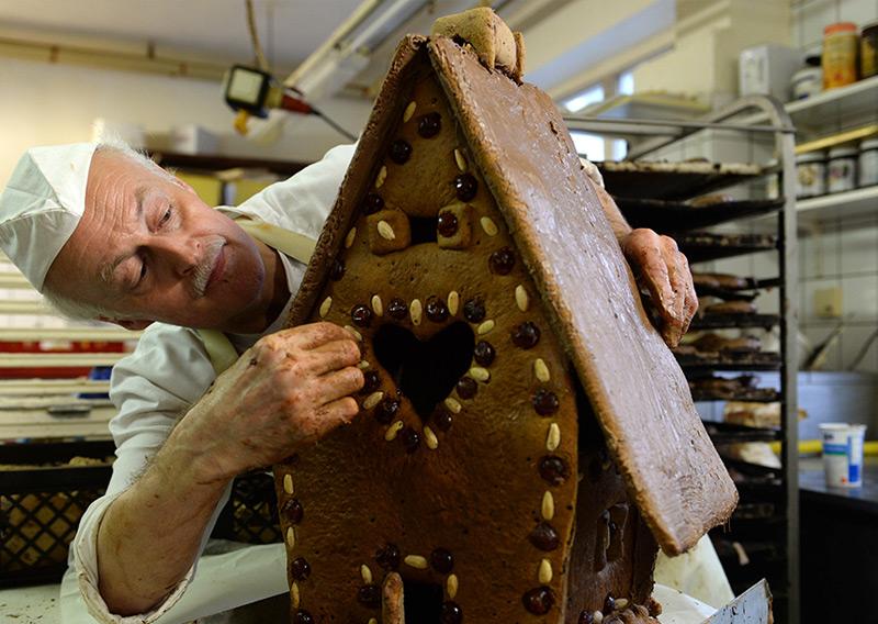 Ein Bäcker mit seinem Lebkuchenhaus