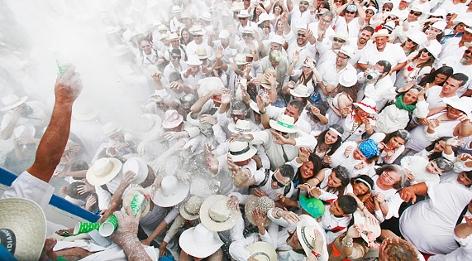Leute werfen weißes Takumpulver in eine Menschenmenge