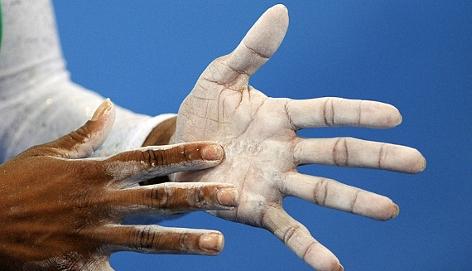 Eine Sportlerin bestäubht ihre Hände mit Talk