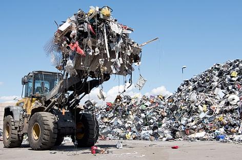 Ein Traktor mit Baggerschaufel transportiert Elektroschrott auf einem Lagerplatz