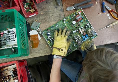 Eine Recycling-Mitarbeiter entfernt Metallteile aus einer Platine