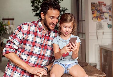 Vater und Tochter schauen auf ein Smartphone