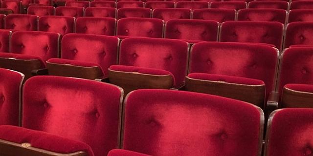 Rotsamtene Sessel in einem Kinosaal