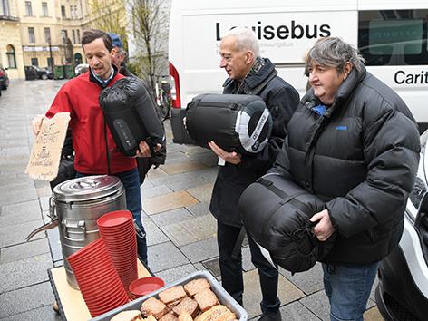 (v.l.) Caritas Wien-Generalsekretär Klaus Schwertner, Caritas-Direktor Michael Landau sowie Gruft-Mitarbeiterin Frau Rosi tragen Schlafsäcke und Lebensmittel, Winterpaket