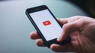 Person hält Handy beziehungsweise Smartphone in der Hand. Darauf sieht man Youtube
