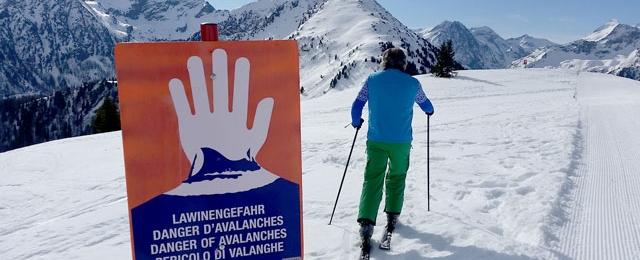 Skifahrer neben Lawinenwarntafel