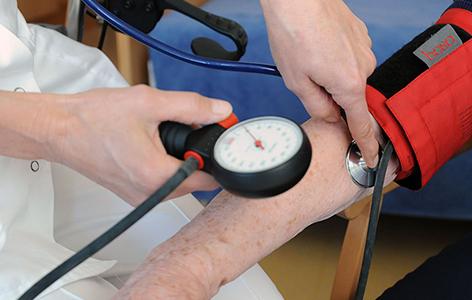 Eine Ärztin misst bei einer alten Frau den Blutdruck.