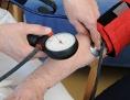 Eine Ärztin musst bei einer alten Frau den Blutdruck.