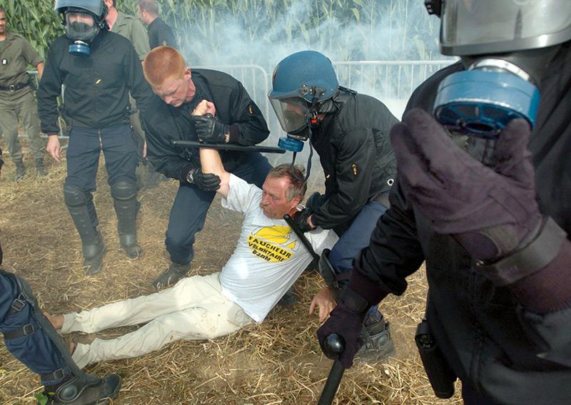 Jose Bové wird von der französischen Polizei beim Versuch festgenommen, ein Feld mit gentechnisch verändertem Getreide zu zerstören