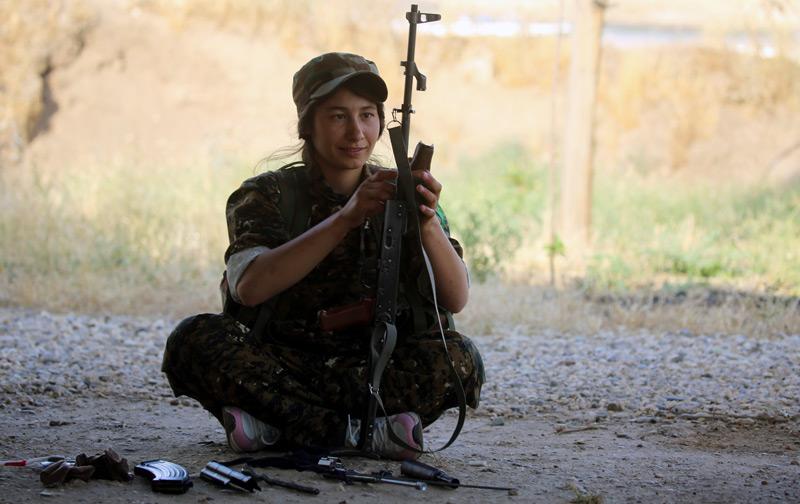 Kurdische Kämpferin mit Gewehr sitzt am Boden