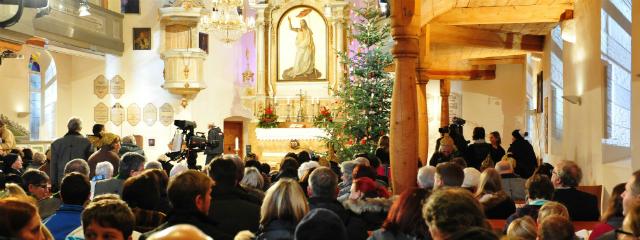 Blick Richtung Altar in weihnachtlich geschmückter Kirche mit vielen Menschen in den Bänken