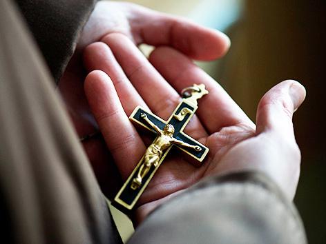 Eine Ordensfrau hält ein Kruzifix in den Händen
