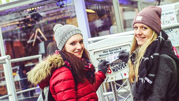 Zwei Mädchen vor dem Spendenbriefkasten