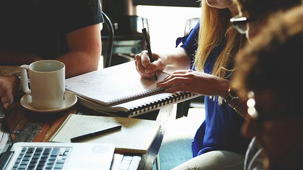 Junge Menschen sitzen um einen Tisch