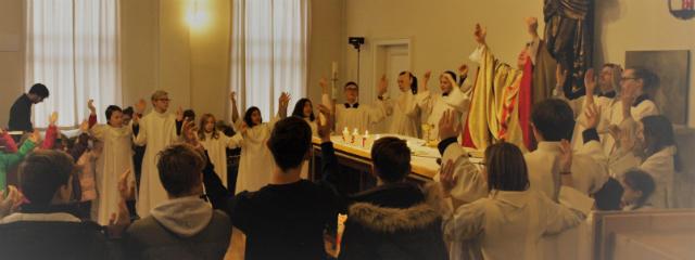Gemeinde im Kirchenraum während eines Gottesdienstes, Priester hebt die Arme