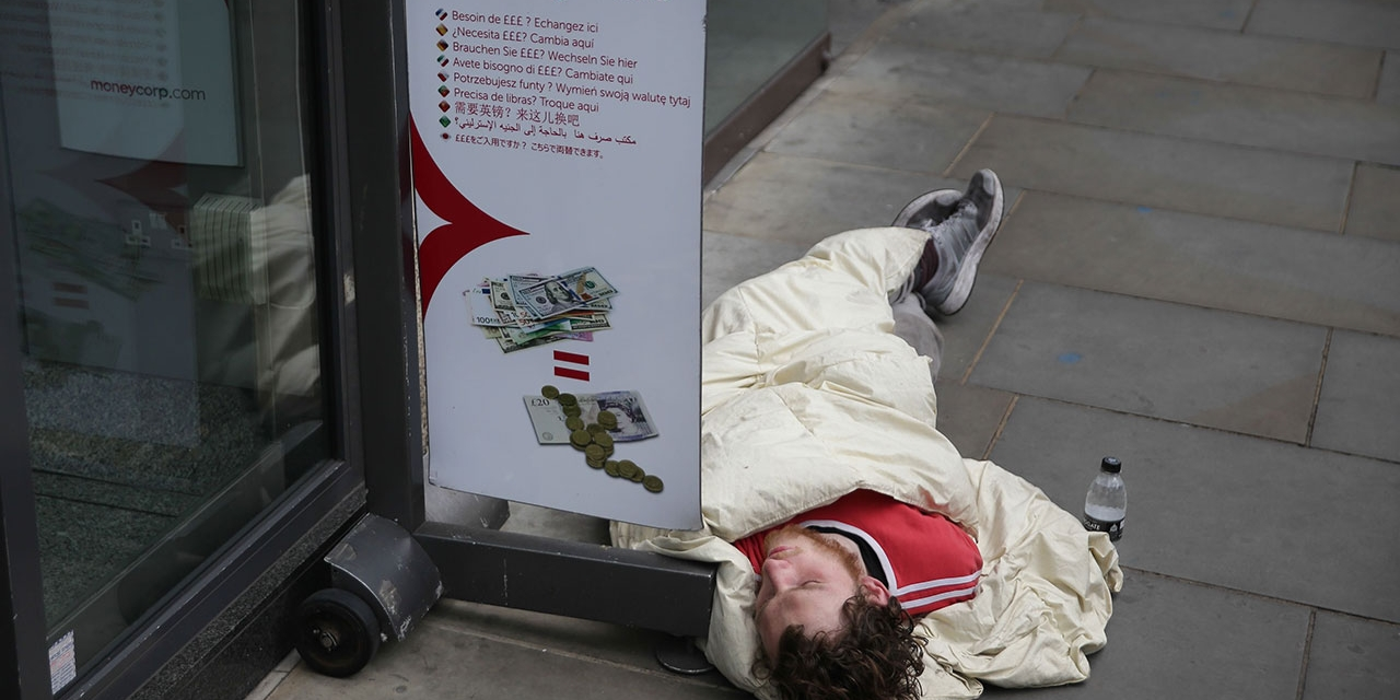 A homeless person sleeps by the entrance to a money exchange shop in central London on May 16, 2017