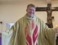 Priester im Festgewand mit einladend ausgebreiteten Armen