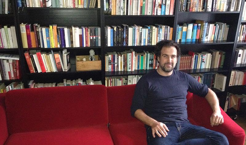 Historiker Eugen Pfister sitzt auf einer Couch vor einer Bücherwand